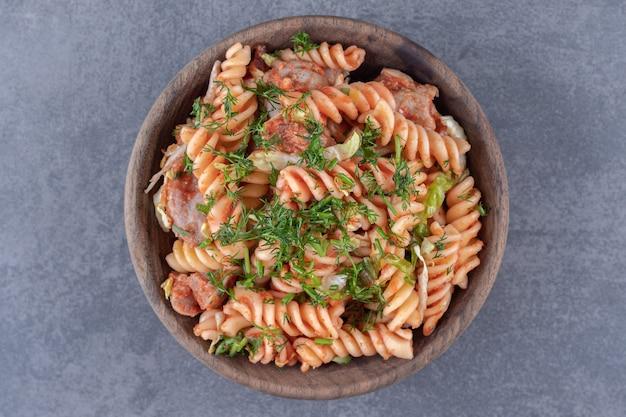Delicious fusilli pasta in wooden bowl.