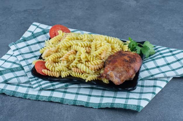 Fusilli deliziosi con pollo sul piatto scuro.