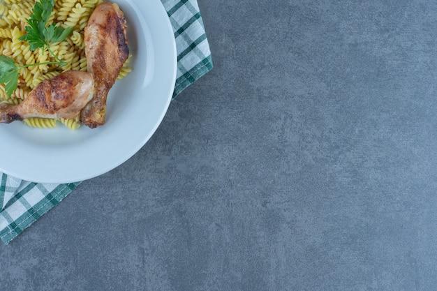 하얀 접시에 닭 다리가 있는 맛있는 푸실리.
