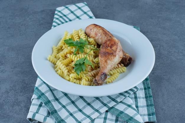Fusilli deliziosi con cosce di pollo su piatto bianco.