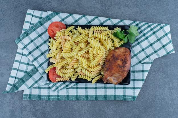 Вкусные фузилли с курицей на темной тарелке.