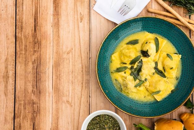 Ravioli deliziosi di contorno in piatto di ceramica verde su superficie di legno