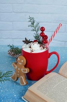 おいしいジンジャーブレッドクッキー、本、青い背景の上のコーヒーの赤いカップ。高品質の写真