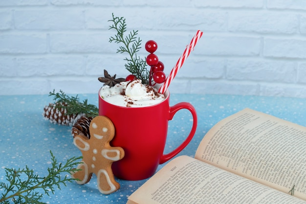 Delicious gingerbread cookie, book and red cup of coffee on blue surface. .
