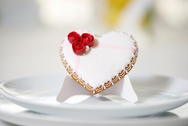 흰색 달콤한 유약으로 덮여 있고 작은 빨간 장미와 흰색 작은 진주로 장식 된 맛있는 진저 쿠키가 흰색 접시와 함께 테이블에 선다. 축제 결혼식 테이블을위한 좋은 장식.
