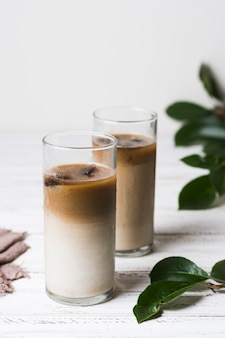 Delicious glasses with coffee and ice cubes