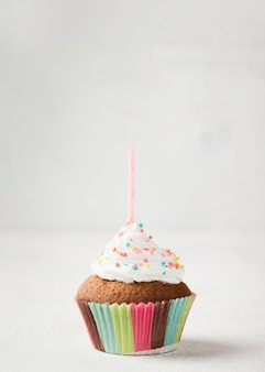 Muffin glassato delizioso con la candela