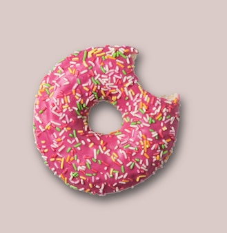 Delicious glazed pink bite doughnut with sprinkles on gray  background. top view. concept food