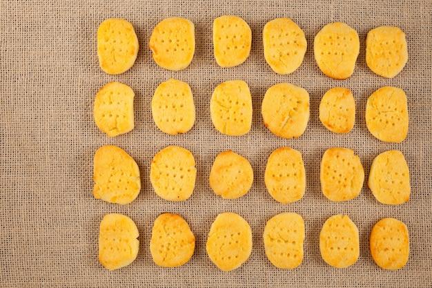 上から見ると、グルテンフリーのおいしい自家製クッキーが黄麻布の上に均等に並んでいます。