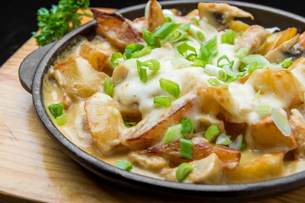 패스트 푸드 카페에서 맛있는 황금 감자 튀김. 건강에 좋지 않지만 맛있는 정크 푸드. 베이컨과 치즈 튀김 감자 스틱