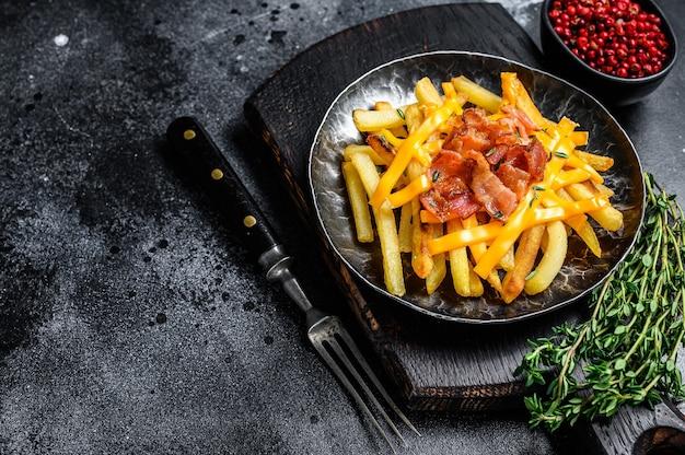 녹은 체다 치즈와 베이컨으로 맛있는 황금 감자 튀김. 검정색 배경. 평면도. 공간을 복사하십시오.