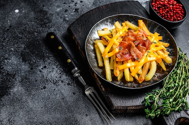 Delicious golden french fries with melted cheddar cheese and bacon. black background. top view. copy space.