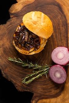 Вкусный гамбургер для гурманов. гамбургер с поджаренным и хрустящим хлебом, плавленым сыром, луком, розмарином травы на деревянном столе. вид сверху