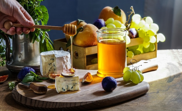 Delicious gourmet cheese dorblu, honey, with sliced fresh figs and grapes, peaches, on a rustic wooden table