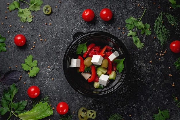 トマト、オリーブ、新鮮なハーブを使ったおいしいギリシャ風サラダ、ダークストーンのテーブルにあるファーストフードレストランのメニューにある新鮮なサラダ。ファーストフードの健康的なオプション。