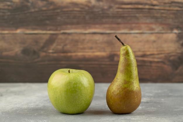 Вкусное зеленое яблоко и свежая груша на мраморной поверхности.