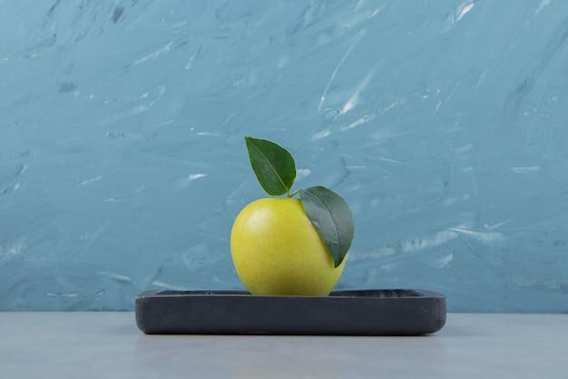 Вкусное зеленое яблоко на черной тарелке.