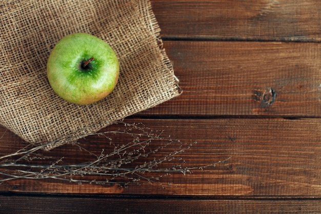 Delicious green apple on a wooden table. top view background