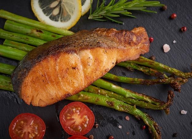 Вкусная зеленая спаржа и нарезанный копченый лосось на деревенской тарелке