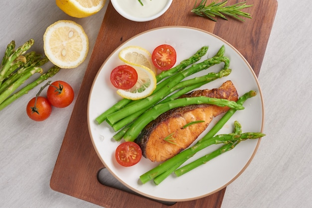 Delicious green asparagus and sliced smoked salmon on a rustic plate