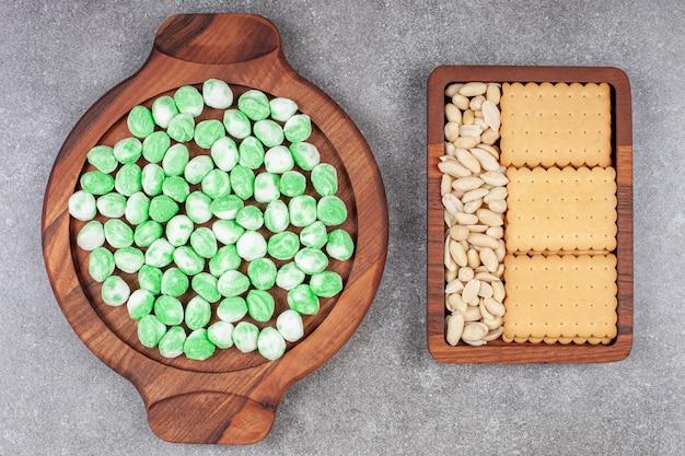 Вкусные зеленые конфеты и печенье на мраморной поверхности