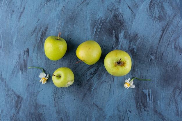 青いテーブルの上に置かれたおいしい緑の新鮮なリンゴ。