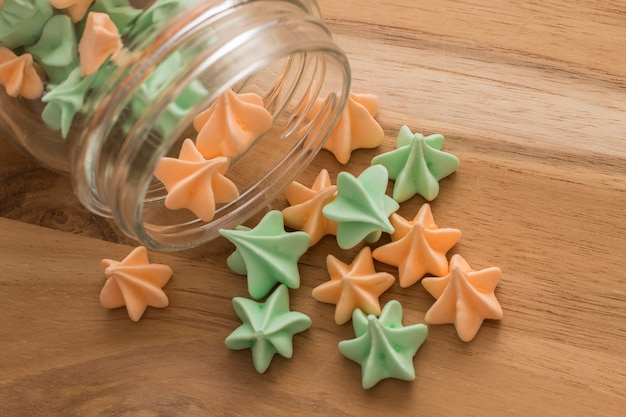 Delicious green and orange meringue on wooden background.