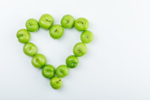Вкусные зеленые сливы на белой стене. вид сверху.