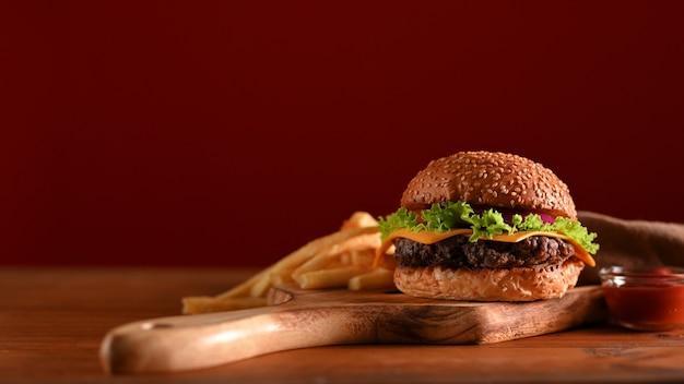 赤い壁のファストフード店のテーブルの上の木製トレイでおいしい牛肉のグリルハンバーガーとフライドポテトを提供