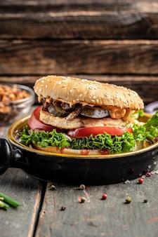 チキン、ピクルス、揚げタマネギを添えたおいしいグリルバーガー。木製の背景にビーフバーガー。ファーストフードとジャンクフードのコンセプト