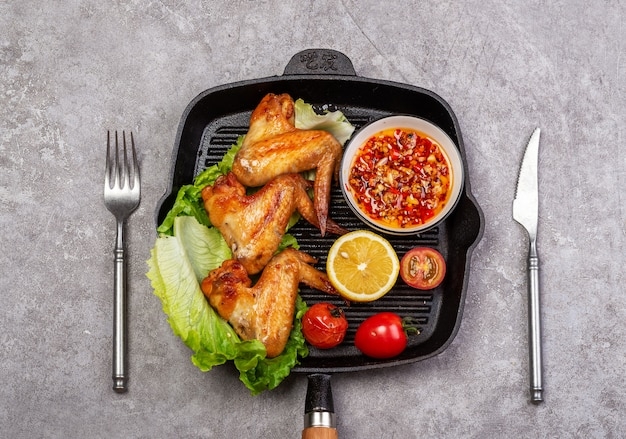 Delicious grilled chicken wings and vegetable salad