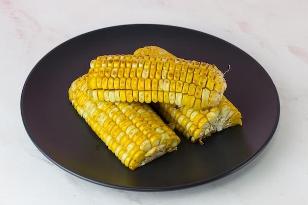 흰색 배경에 검정 접시에 맛있는 구운 옥수수 속대
