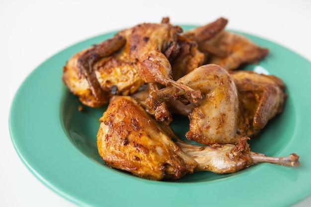 На зеленой тарелке лежат вкусные жареные на гриле перепела. вкусное и полезное мясо.
