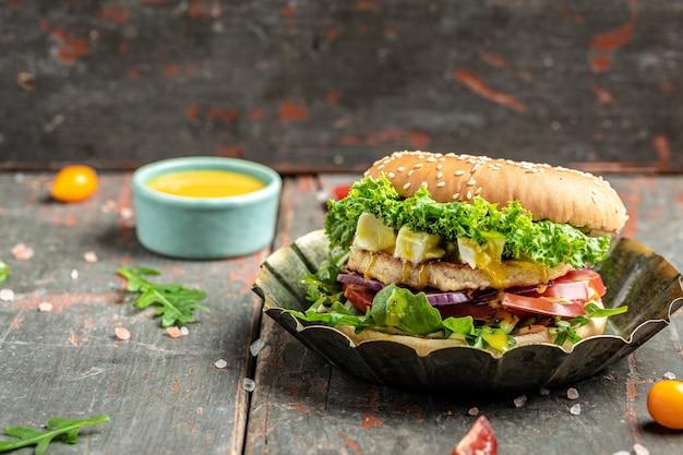 木製のテーブルにフェタチーズとチキンビーフを添えたおいしいハンバーガーのグリル。不健康な栄養をもたらすダイエット誘惑の象徴。テキストの場所。
