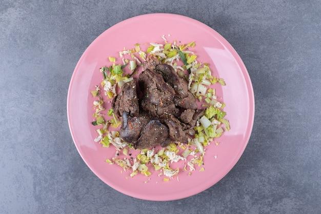 Delizioso kebab alla griglia sul piatto rosa.