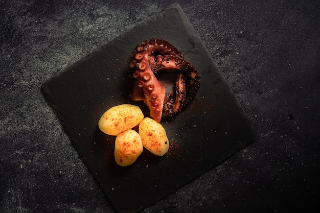 Delicious grilled octopus tentacles with potatoes seasoned with spanish paprika, olive oil, and sea salt