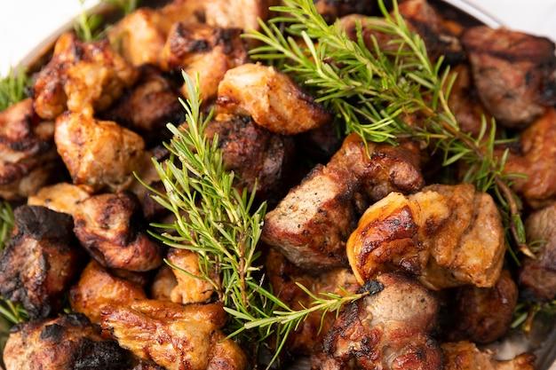 그릴에 구운 맛있는 고기 조각이 허브로 장식된 접시에 놓여 있습니다. 선택적 초점입니다.