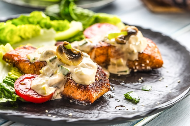 Вкусные жареные филе лосося или стейки с грибным соусом, кунжутом, помидорами и салатом.