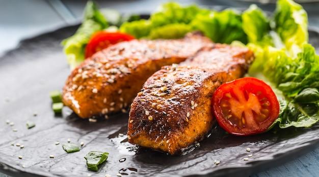 Вкусные жареные филе лосося или стейки с помидорами кунжута и салатом.