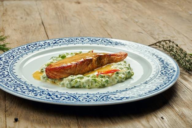 Вкусный стейк из лосося на гриле с горохом в сливочном соусе в белой тарелке на деревянной поверхности. вкусные морепродукты