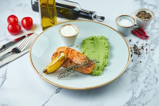 Delicious grilled salmon steak with white sauce, garnished with mashed peas in a blue plate on a marble surface