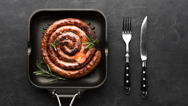 Вкусная жареная колбаса на сковороде со столовыми приборами