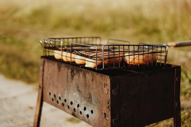 Вкусные колбаски на гриле, лежащие на железной решетке переносного барбекю над раскаленными углями, пока они готовятся безупречно.