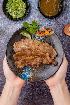 Вкусная нарезанная на гриле свиная грудинка с соусом барбекю или барбекю на тарелке