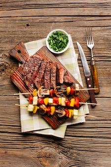 Delicious grilled steak and meat skewer on wooden cutting board over textured backdrop
