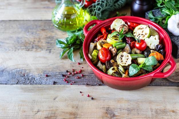 木製の背景に鍋でおいしい焼き野菜。健康食品のコンセプト。コピースペース