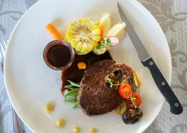 Delicious grilled wagyu tenderloin steak with red wine sauce and vegetable on white plate