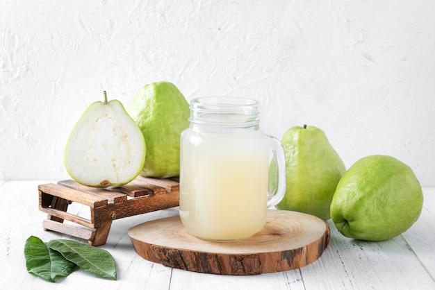 밝은 흰색 나무 테이블 배경에 신선한 주스와 함께 맛있는 구아바 과일