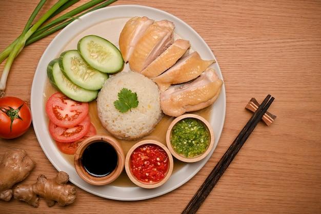 おいしい海南チキンライスは、3つのソースとキュウリとトマトのスライドで提供されます