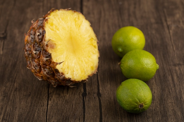 Delicious half sliced fresh pineapple and limes on wooden surface.